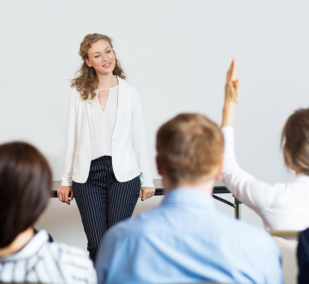 Smiling young businesswoman leaning on table and looking at woman from audience raising hand. Rear view of audience of five people.